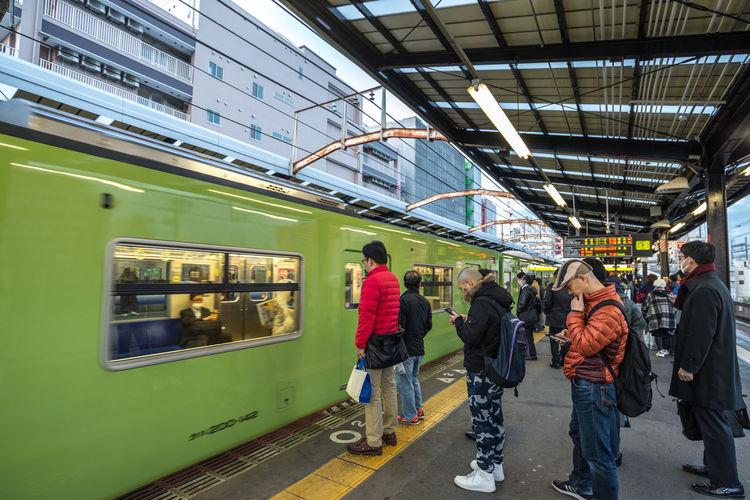 People waiting train at railroad station platform