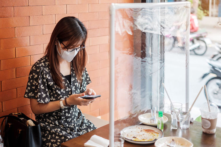 Woman using smart phone sitting at cafe