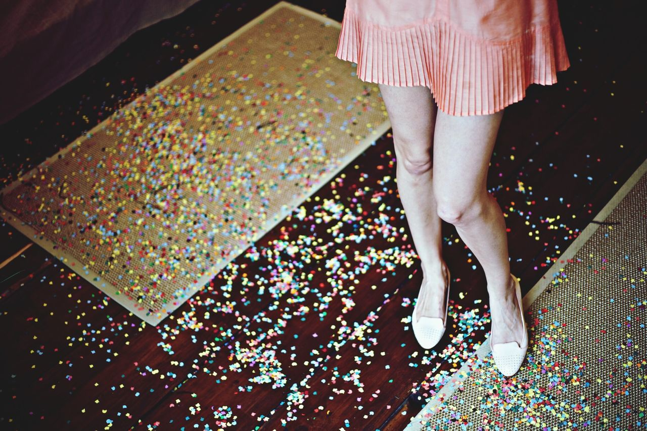 Low section of woman in short skirt with confetti on floor