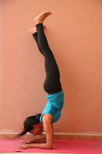 Young woman practicing handstand by wall
