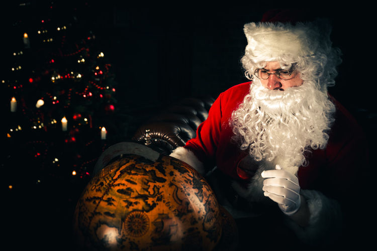 Man wearing santa claus costume looking at globe at home