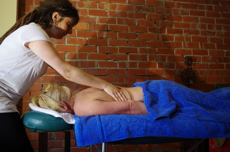Young Massage Therapist Rubbing Back Of Woman At Health Spa