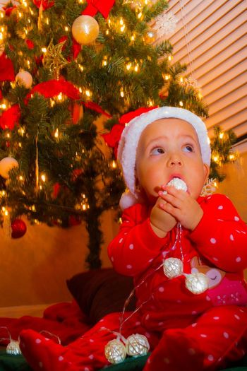 Cute Girl By Illuminated Christmas Tree At Home