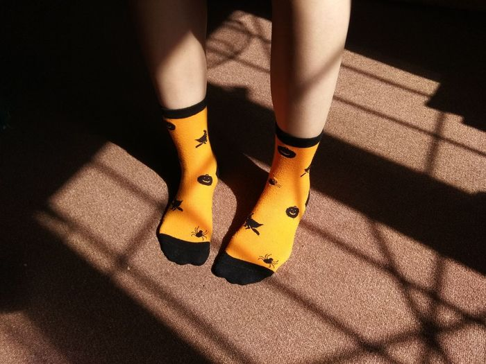 Low section of woman wearing yellow socks while standing on carpet at home