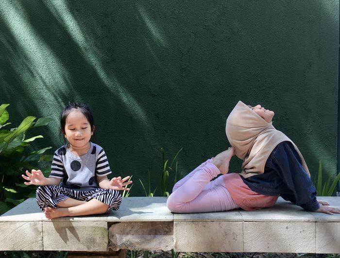Smiling girls sitting outdoors
