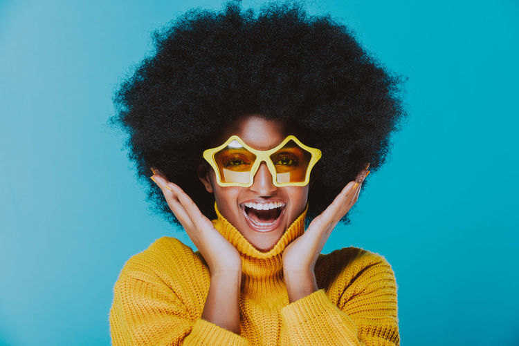 Portrait of happy young woman wearing sunglasses against blue background