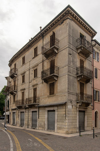 a old and shabby house in verona, italy Architecture Balcony Building Building Exterior Built Structure City Cloud - Sky Day Low Angle View No People Old Outdoors Residential District Ruin Scary Shabby Sky Window