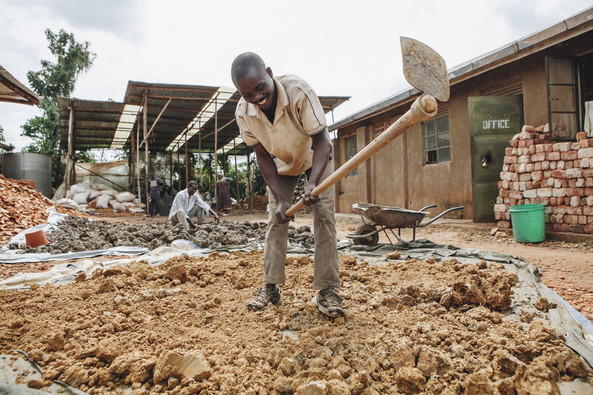 Adult Adults Only Africa African Bricks Ceramic Clay Day Dirt Factory Ground Hoe Manual Labor Manual Worker Manufacturing Men Mud Outdoors People Poor  Poverty Wheelbarrow Woman Working Workshop