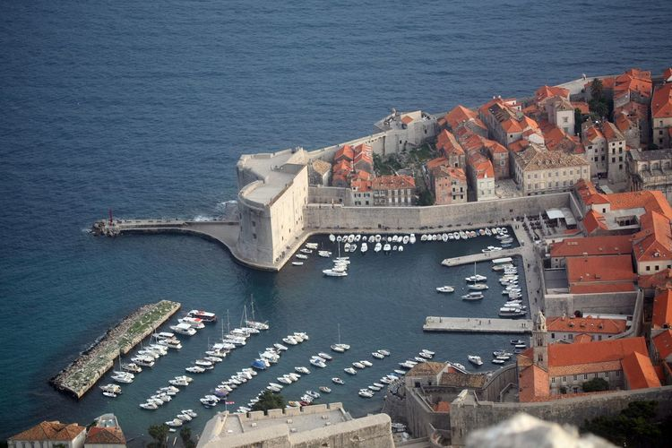 High angle view of townscape by harbor on sea