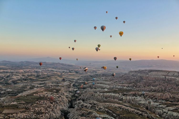 Hot air balloons flying over landscape against clear sky during sunset