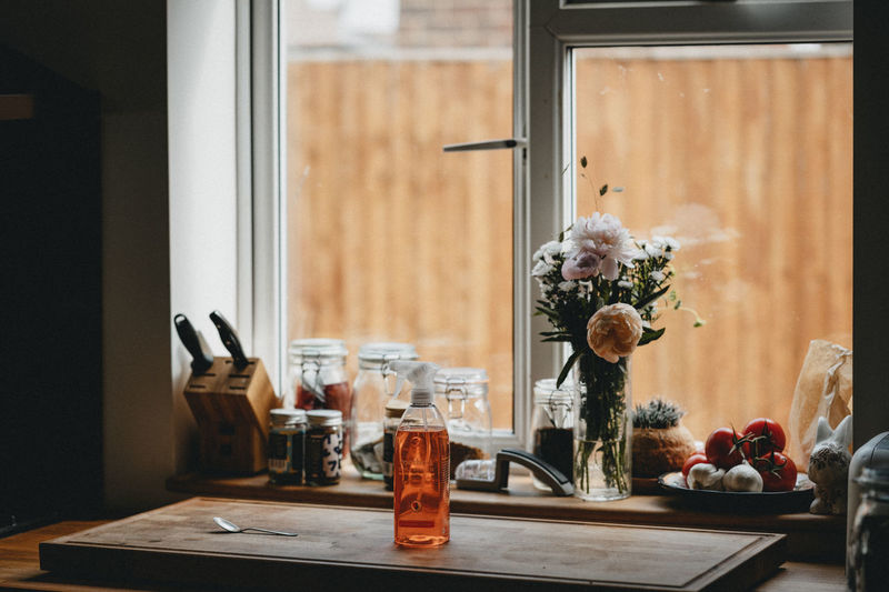 Flower vase with spices on window sill at home