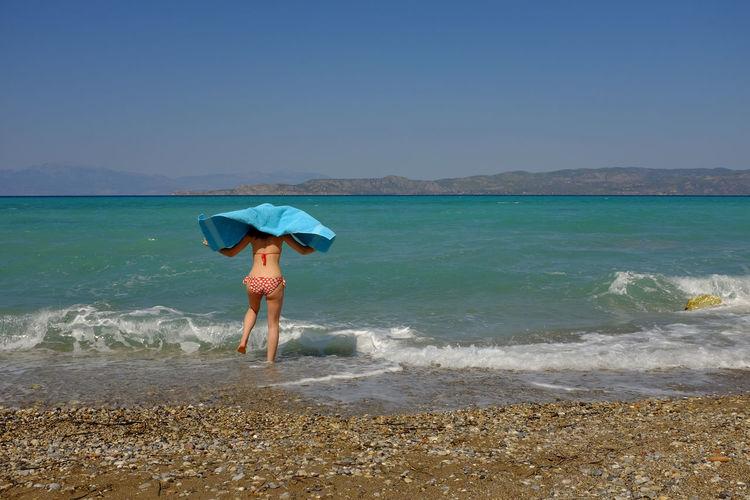 Rear View Of Woman In Bikini Walking On Beach Against Clear Sky