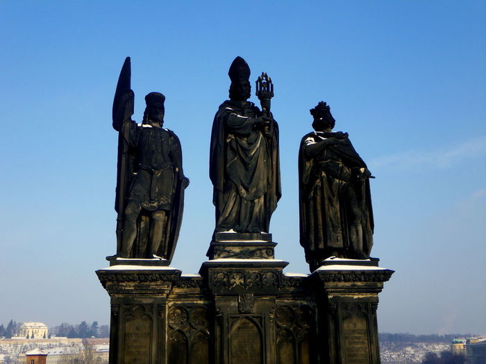 Low angle view of statues at on charles bridge against sky