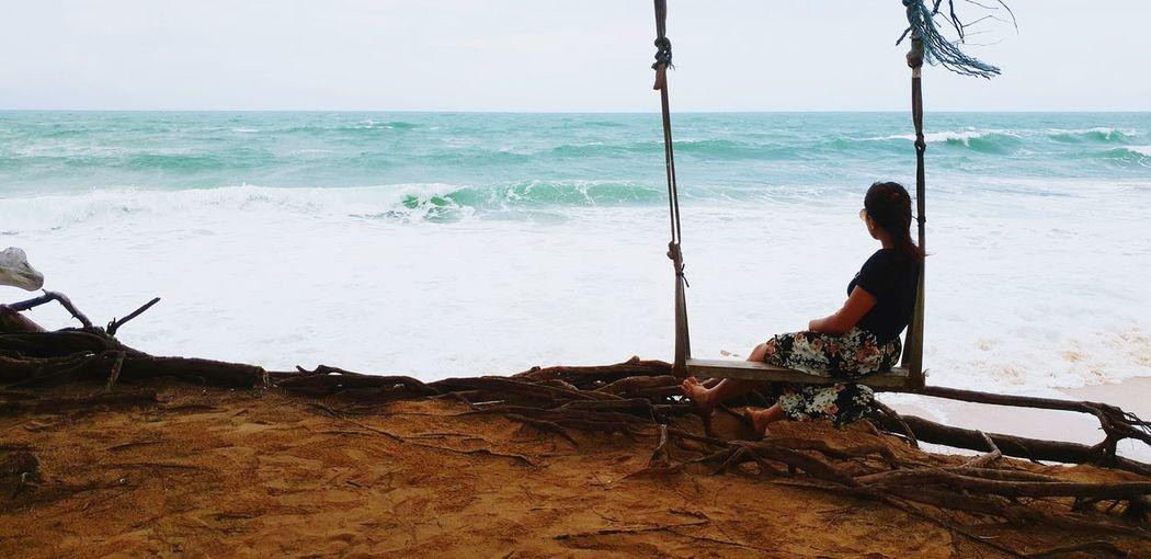 Woman sitting on swing at beach