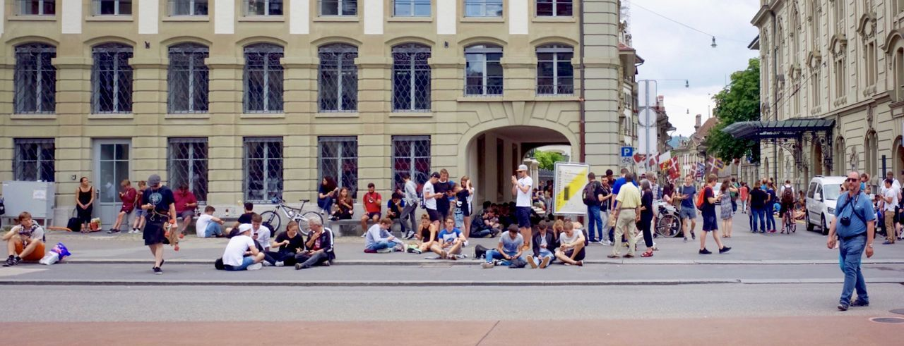 Panoramic View Of People On Sidewalk In City