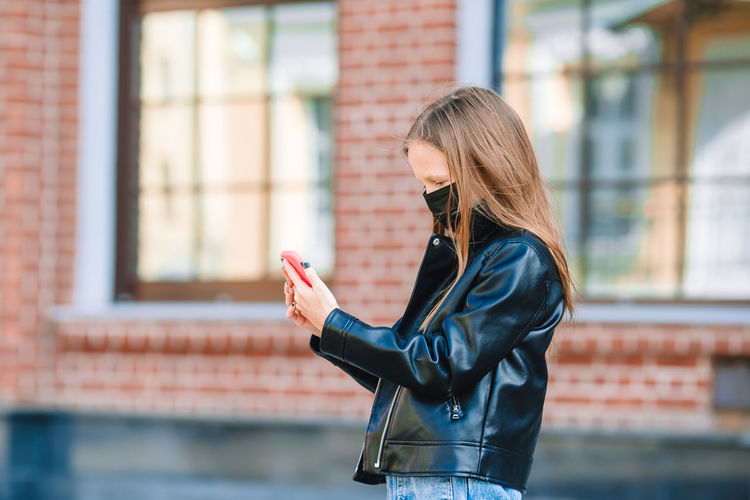 Girl wearing mask while using phone