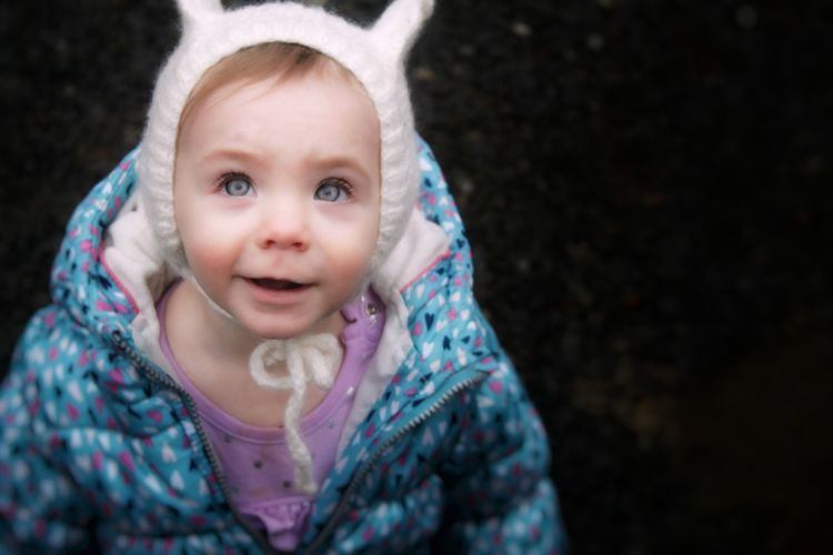 Close-up portrait of baby girl in warm clothes over back background