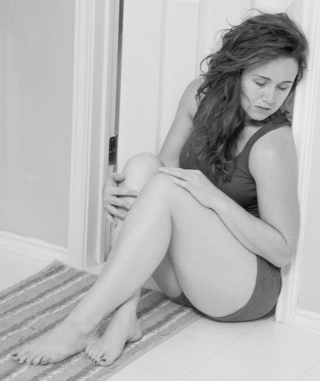 Full length of mature woman sitting by wall at home