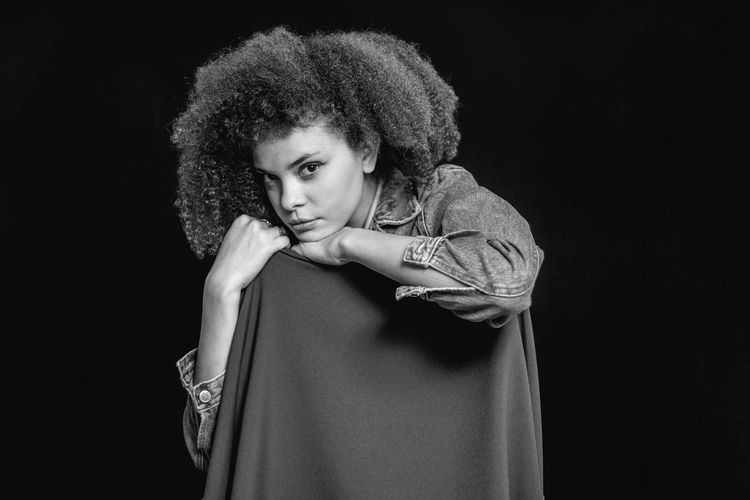Portrait of young woman standing against black background