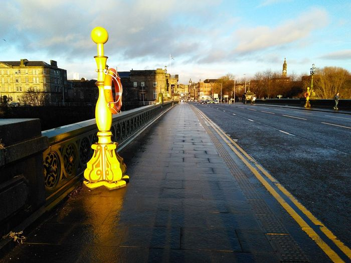 a vibrant yellow post at the shoulder of a bridge Bridge Post Road Shoulder City Yellow Road Urban Skyline Cityscape Sky Architecture Built Structure Cloud - Sky Bare Tree vanishing point Road Marking Puddle Empty Road RainDrop