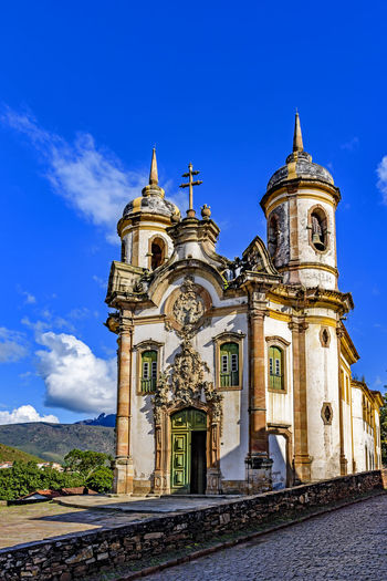 Facade of the church of São Francisco de Paula in Ouro Preto, Minas Gerais with its windows, large wooden door, stone arch, towers, and baroque sculptures 18 Century Brazil Cathedral Church Minas Gerais Ouro Preto UNESCO World Heritage Site Architecture Baroque Style Building Building Exterior Built Structure Colonial Architecture History No People Outdoors Place Of Worship Religion Rococo Sky Spirituality The Past Tower Towers Travel Destinations