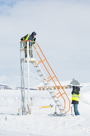People working on snow covered field against sky