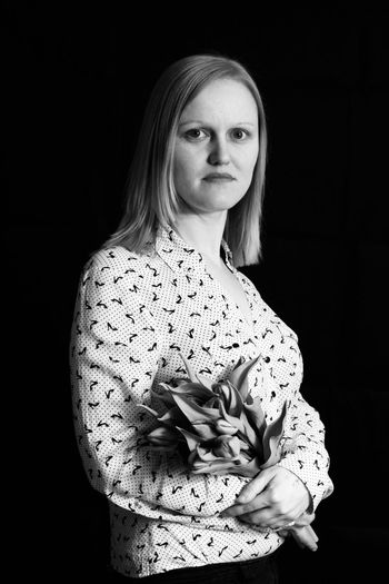 Portrait of beautiful mid adult woman with bouquet standing over black background