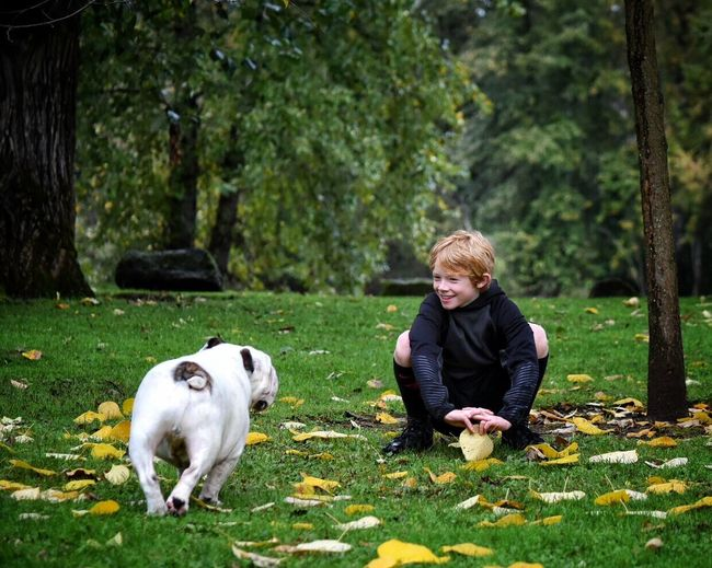 Full length of dog and boy on grassy field