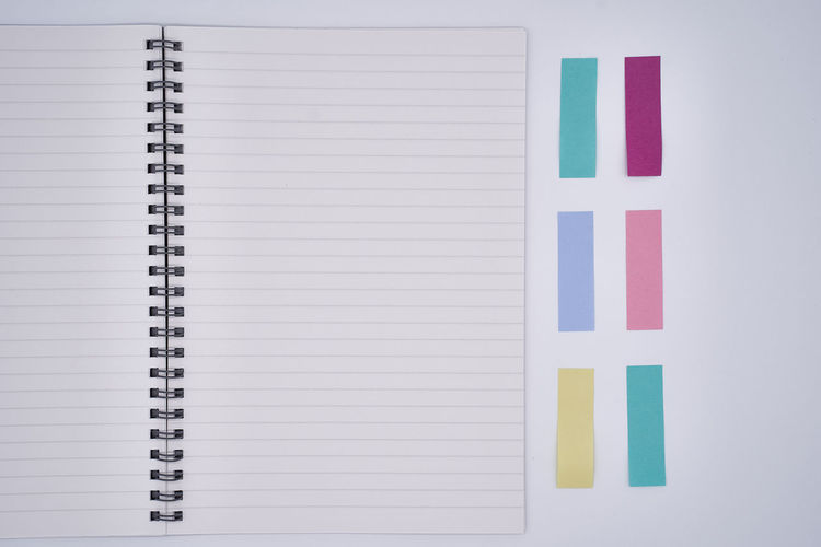 Directly above of spiral notebook with adhesive notes on gray background