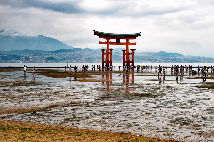 People At Torii Gate On Shore Against Cloudy Sky