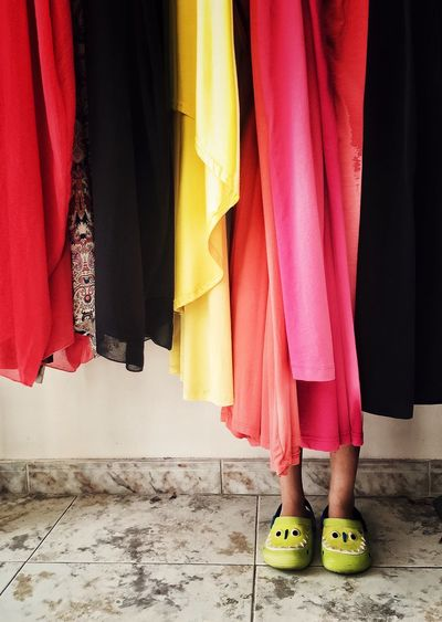 Low section of person hiding behind multi colored fabrics