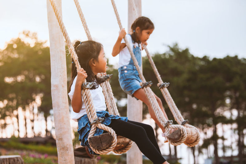 Sisters swinging at playground
