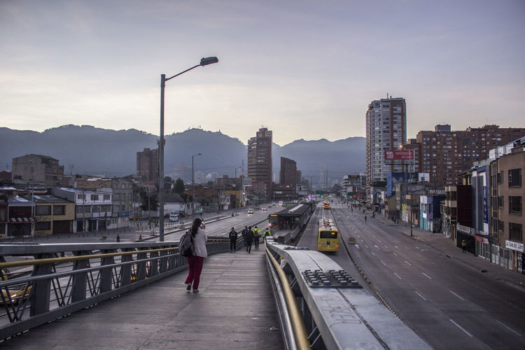 Woman Walking On Bridge Against Sky During Sunset