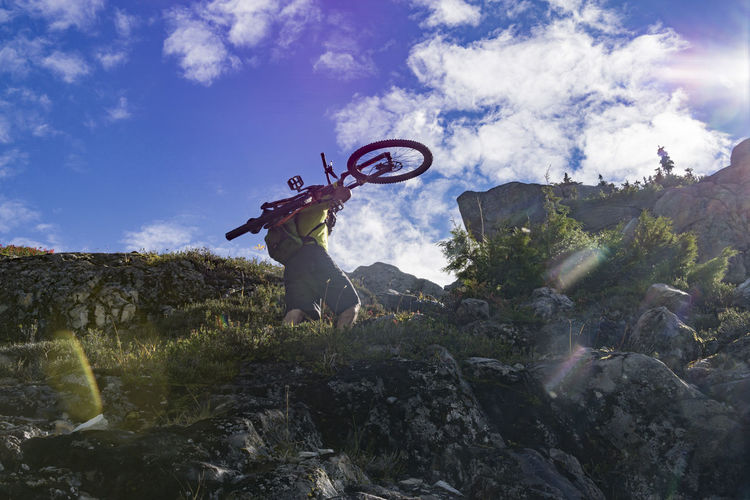 Man Carrying Bicycle Up Mountain