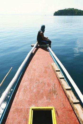 Man Sitting On Ship's Bow