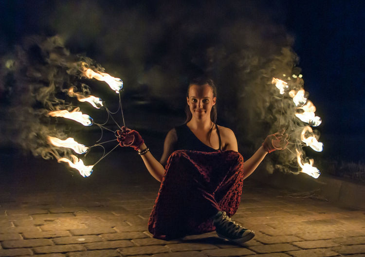 Portrait of fire dancer holding burning equipment at night