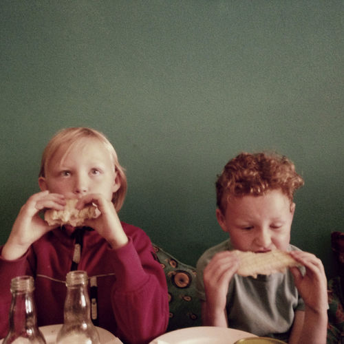 Two children eating sandwiches. Brother Childhood Food And Drink Indoors  Innocence Sister Togetherness Two People