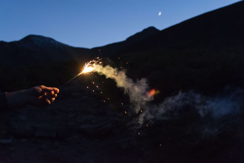 Cropped hand of person holding sparkler against mountain at night