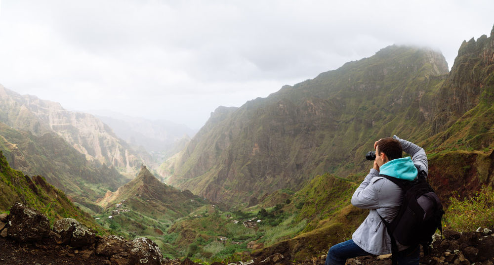 Traveler on the mountain edge making a photo of landscape. Deep clouds above green Xo-Xo Valley. Santo Antao Island, Cape Verde. Cape Verde Activity Beauty In Nature Casual Clothing Holding Camera Hood - Clothing Leisure Activity Lifestyles Looking At View Mountain Mountain Range Nature Non-urban Scene One Person Outdoors Photography Real People Rear View Scenic Landscapes Scenics - Nature Sitting Sky Technology Tranquil Scene Tranquility