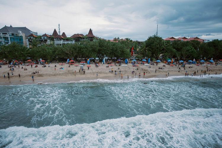 Group of people in sea against sky