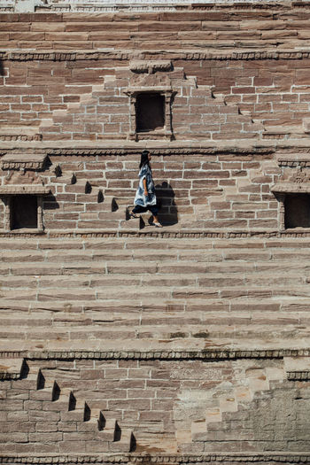 Side view of woman on staircase against brick wall