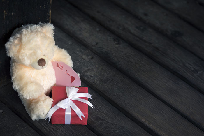 Red gift box with white tied bow and a cute teddy bear toy holding a message on a rustic wooden floor Love Messages Valentine's Day  Childhood Christmas Close-up Cute Message Gift Gifting Time High Angle View Lovely Paper Messages Red Gift Sharing  Stuffed Toy Teddy Bear Tied Bow Toy Wooden Floor