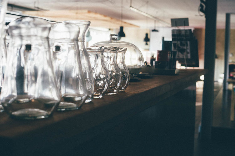 Empty glass jugs on counter at bar
