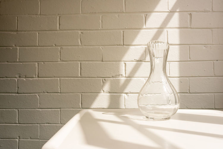 Glass vase with shadows Wall - Building Feature Indoors  Shadow No People Glass - Material Sunlight Transparent Wall White Color Still Life Nature Close-up Brick Wall Brick Simplicity Empty Water Built Structure Crockery