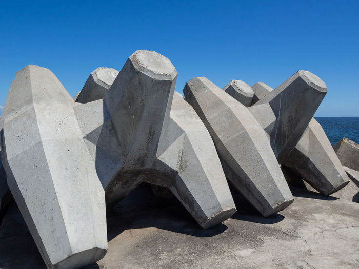View of concrete and sea against blue sky