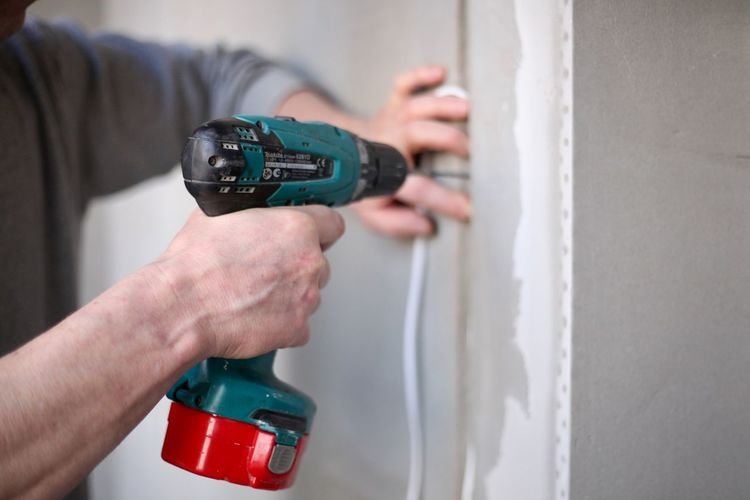 Close-up of man working against wall