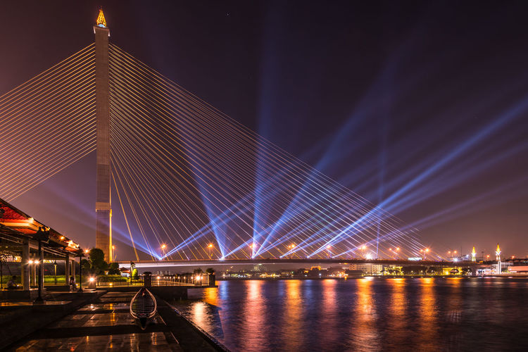 Illuminated rama viii bridge over river against sky at night in city