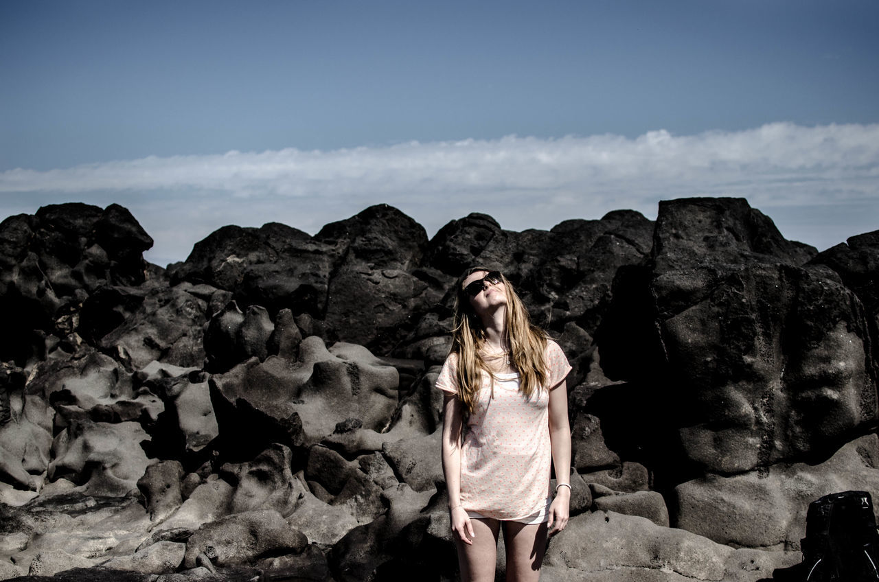 Beautiful young woman looking up against rocks and sky