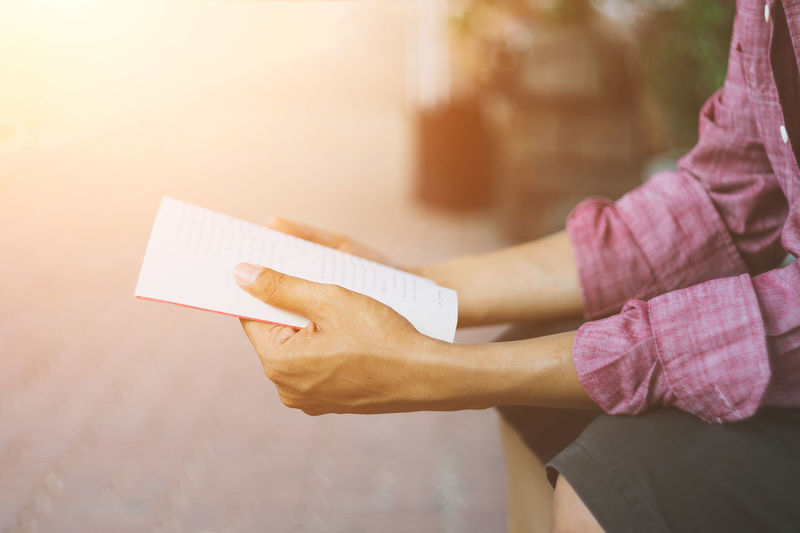 A man is reading a book outside his room in free time. Reading A Book Reading & Relaxing Reading Glasses Reading Book Book Adult Casual Clothing Close-up Communication Copy Space Day Hand Holding Human Hand Lifestyles One Person Paper Women Capital Letter Friend