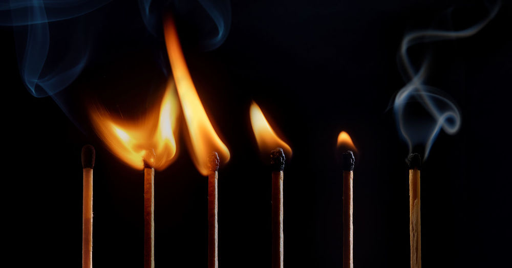 Close-up of burning candles against black background